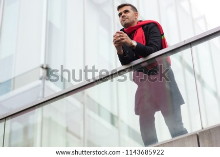 Introspective inspired young man leaning on glassy railing and looking into distance. Serious pensive handsome businessman in red scarf lost in thoughts during stroll. Alone with thoughts concept