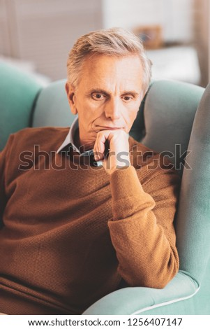 Introspective man. Aged introspective man feeling thoughtful while thinking about some difficult assignments
