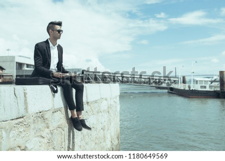 Introspective successful man on business trip. Calm handsome young student in sunglasses contemplating waterscape while resting on pier alone. Loneliness concept