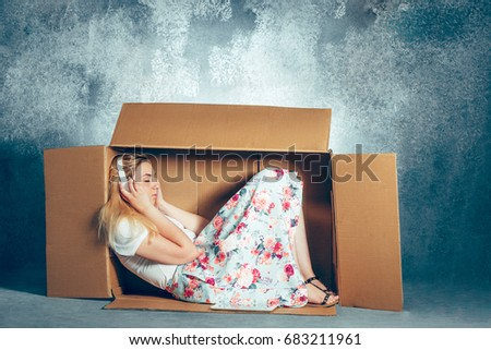 Introvert concept. Woman sitting inside box and working with laptop