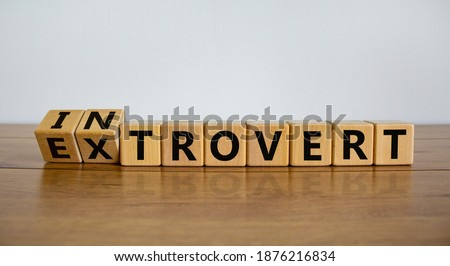 Introvert or extrovert symbol. Fliped cubes and changed the word 'introvert' to 'extrovert'. Beautiful wooden table, white background, copy space. Psychological and Introvert or extrovert concept. Foto stock ©