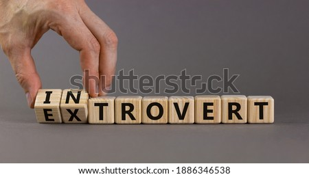 Introvert or extrovert symbol. Hand turns cubes and changes the word 'introvert' to 'extrovert'. Beautiful grey background, copy space. Psychological and Introvert or extrovert concept. Foto stock ©