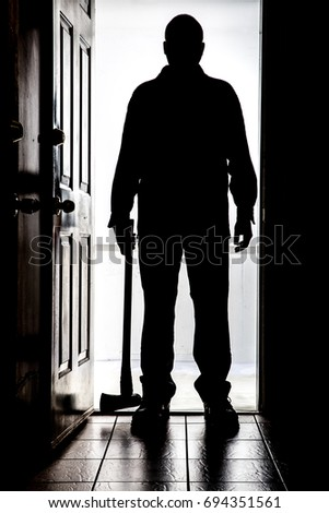 Intruder standing at doorway threshold, in silhouette with axe