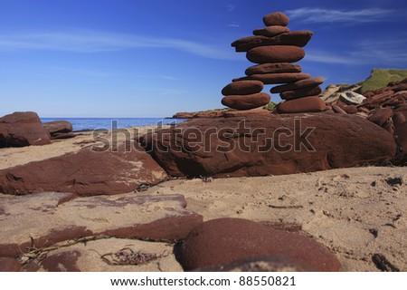 Inukshuk made of Red rocks on a Prince Edward Island Beach Canada