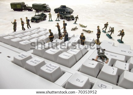 Invading force of miniature army toy soldiers in an attack on a computer keyboard as a metaphor for the risk of virus and worm infection in internet or network security