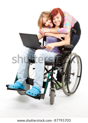 invalid girl on the wheelchair with laptop and her friend - stock photo