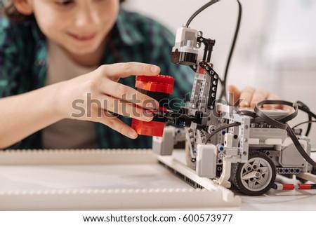 Inventive teen kid constructing robot in the studio