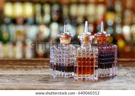 Inventory of the bartender at the bar counter - droppers for bitters and syrups stand in a row on a blurred background of the bar