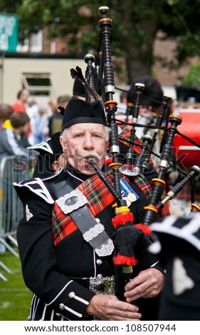INVERNESS, SCOTLAND - JULY 21: An unidentified member of The Royal British Legion Pipe Band takes part in the annual Inverness Highland Games in Inverness, Scotland on July 21, 2012.