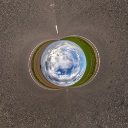 Inversion of blue little planet transformation of spherical panorama 360 degrees. Spherical abstract aerial view on road with awesome beautiful clouds. Curvature of space.
