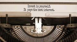Invest in yourself symbol. Text 'invest in yourself it pays the best interest' typed on retro typewriter. Business and invest in yourself concept. Beautiful background. Sepia.