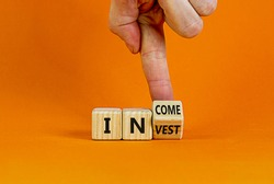 Invest or income symbol. Businessman turns a wooden cube and changes the word 'invest' to 'income'. Beautiful orange background, copy space. Business and invest or income concept.
