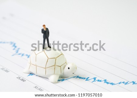 Photo of  Invest with slow but steady for long term success metaphor, miniature people businessman riding turtle or tortoise walking on rising growth stock market value graph, value investment concept.