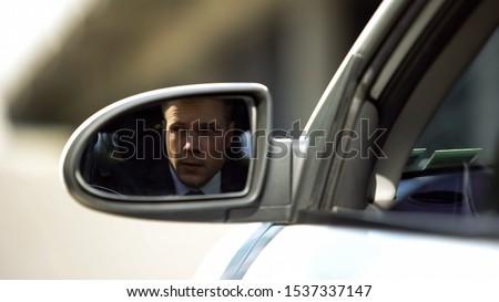 Investigating businessman looking outside car, rear mirror view, suspicion