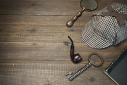 Investigation Concept. Private Detective Tools On The Wood Table Background. Deerstalker Cap, Old Key  And Book, Tobacco  Pipe, Vintage Magnifying Glass. Overhead View