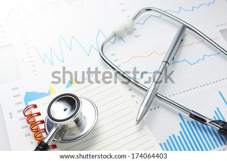 Investigation of daily health conditions. Close up of graphs, stethoscope, notebook and pen.