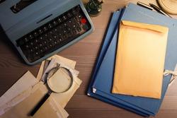 Investigator desk with confidential documents, magnifying glass, vintage typewriter. Secret documents investigation concept.