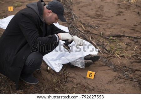 Investigator finds the gun next to the homicide victim.  - Shutterstock ID 792627553
