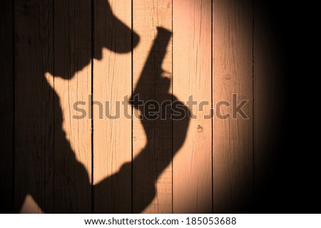 Investigator or Gangster or spy silhouette on natural wooden wall. You can see more silhouettes and shadows on my page. #185053688