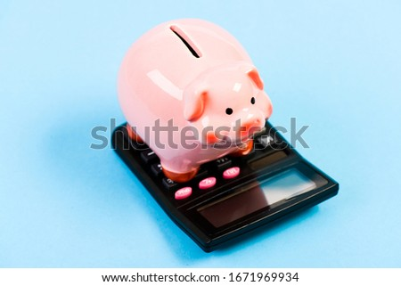 Investing gain profit. Calculate taxes. Piggy bank pig and calculator. Taxes and charges may vary. Accounting business. Pay taxes. Taxes and fees concept. Tax savings. Piggy bank money savings.