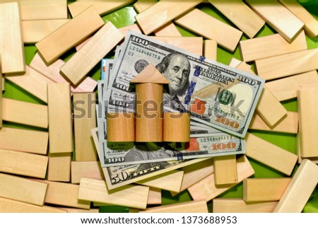 Investing in banks. Sketchy bank building, built on dollar bills, in a box with a wooden constructor. #1373688953