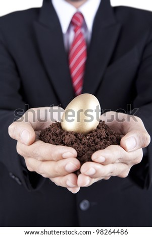Investment concept businessman showing a golden egg and soil