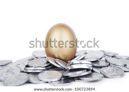 Investment concept: golden egg with coins isolated on white