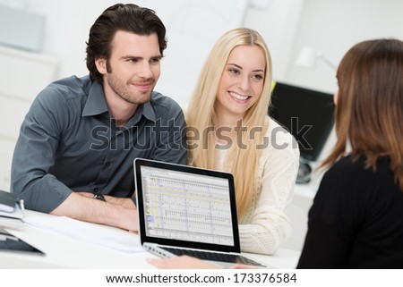 Investment or insurance broker or adviser conducting an interview with a smiling young couple as they plan their future investments