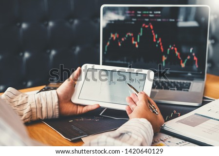 Investment stock market Entrepreneur Business Man using tablet discussing and analysis graph stock market trading,stock chart