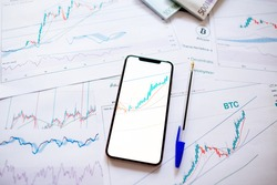 investment stockbroker price trend and profit. Stock market trader analyzing bitcoin price trend. Investment broker trading bitcoin crypto currency using phone and laptop. Multiple devices.