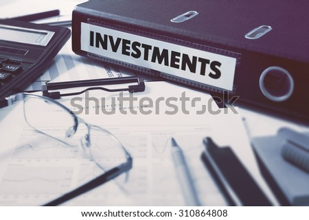 Investments - Office Folder on Background of Working Table with Stationery, Glasses, Reports. Business Concept on Blurred Background. Toned Image.