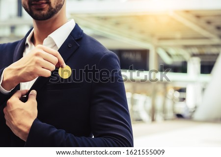 Photo of  Investor beard guy showing bitcoin in a city. White collar worker put bitcoin to suit pocket. Young business man is bitcoin mining, can earn a lot of money. Future money and life with bitcoin concept