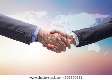 investor businessman handshake together on blur map background for accept in agenda business concept.