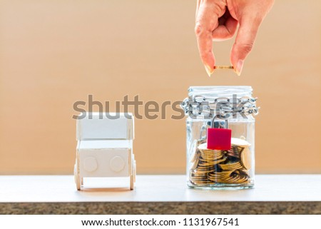 Investor hand hold a gold coin in the jar bank with security with growing and car model put on the desk in the office, loan and saving for buy a new car and business investment property concept. #1131967541