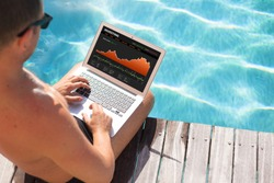Investor looking at stock quotes on laptop by the pool