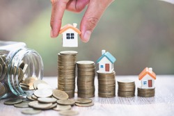Investor show hand holding a model home , Saving money for buy a new house and loan for plan business investment for real estate in the future concept.