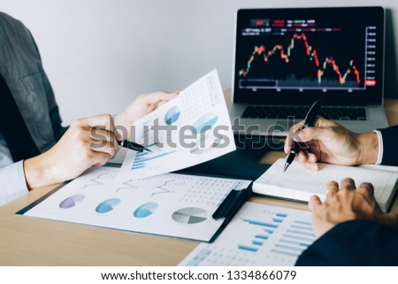 Investors pointed to the company operating results and then shared the results and recorded it in the notebook at the office.