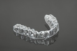 Invisible orthodontics cosmetic brackets on black background. Tooth aligners, for beautiful smile.