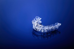 Invisible orthodontics cosmetic brackets on gradient background, tooth aligners, plastic braces. A way to have a beautiful smile and white teeth.
