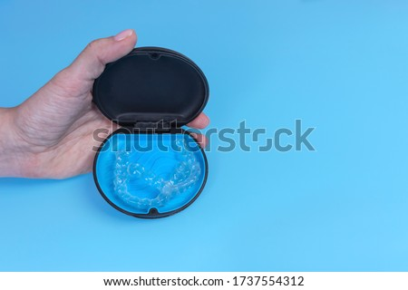 Invisible transparent aligners invisalign in container blue background, clear-plastic retainers. Female woman hand holdinga a black container with retainers inside