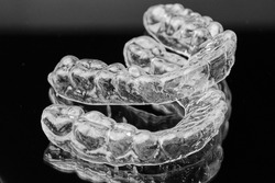 Invisible transparent dental removable braces on the black background. Orthodontic appliance for dental correction. Aligners for teeth straightening.