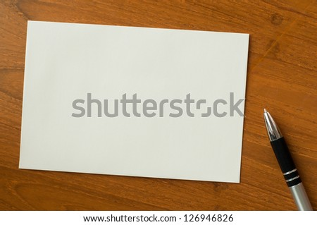 invitation card with pen on wood table
