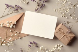 Invitation or greeting card mockup with gift box and dry flowers twigs, stylish top view mockup with copy space