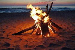 Inviting campfire on the beach during the summer.  Fun and memories at the lake.