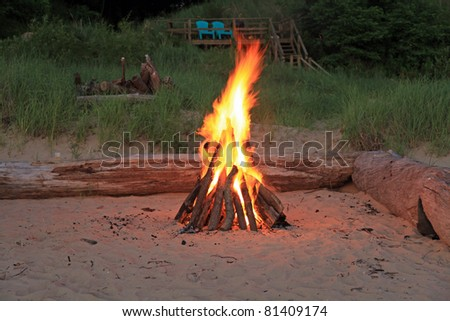 Inviting campfire on the beach on the shore of Lake Michigan in the summer - stock photo