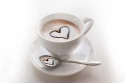 inviting cup of  cappuccino with heart choccolate on top and in the spoon below