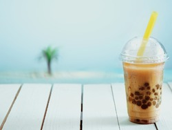 Inviting iced drink in a covered cup on a warm day at the seashore.