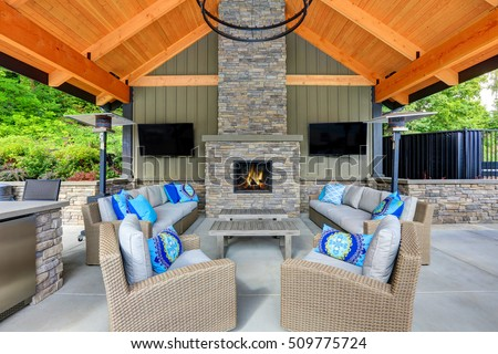 Inviting interior of covered patio area  in Tacoma Lawn Tennis Club. Stone fireplace, wicker furniture with beige cushions and bright blue pillows. Northwest, USA