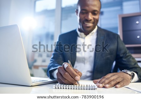 Involved in workflow. Optimistic qualified african businessman in suit is sitting at table with modern laptop and taking some notes in his copybook with smile. selective focus