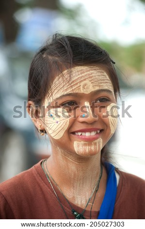 INWA,MYANMAR-JULY 1 : Young Myanmar woman with thanaka on her smile face is happiness on July 1,2014 in Inwa city,Middle of Myanmar.Thanaka is a yellowish-white cosmetic paste made from ground bark.